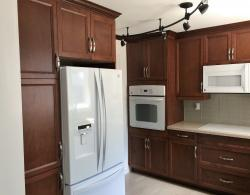 There were no actual structural alterations in this kitchen design by Kestle Interiors.  The fridge was positioned on an existing wall where a portable dishwasher was, with an added pantry unit and over-the fridge cabinets, utilizing the space more efficiently. Full-height wall cabinets provide added storage.  The free-standing dishwasher is replaced by an under-counter unit closer to the sink and prep areas.