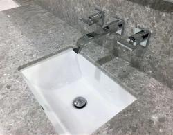 Silestone Ocean Jasper counterop with matching backsplash & wall-mounted faucets
