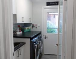White slab-style melamine cabinetry, Slate-colour laminate countertop, Laundry room renovation Kestle Interiors design Newmarket