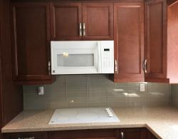 """Quartz countertops, Over-the-range microwave/hood combination, 30"""" ceramic-topped electric cooktop"""
