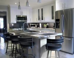 Frost white painted MDF cabinetry, 18 x 18 porcelain floor tile, granite countertop, 36 inch to allow for seating