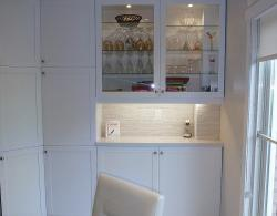 Back-lit glass-fronted wall cabinets with glass shelving