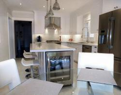 Brilliant White Contemporary Kitchen - An island in this kitchen has replaced the existing peninsula, opening up the kitchen-dining area, creating a more fluid flow from the work-space area through to the dining area.