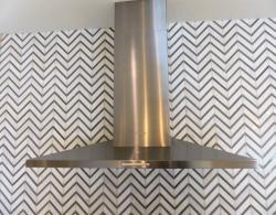 Stainless-steel chimney hood, stone tile, chevron-design backsplash