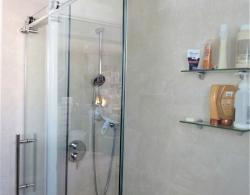 A glass-wall shower with acrylic shower base was added to make this bathroom more functional.